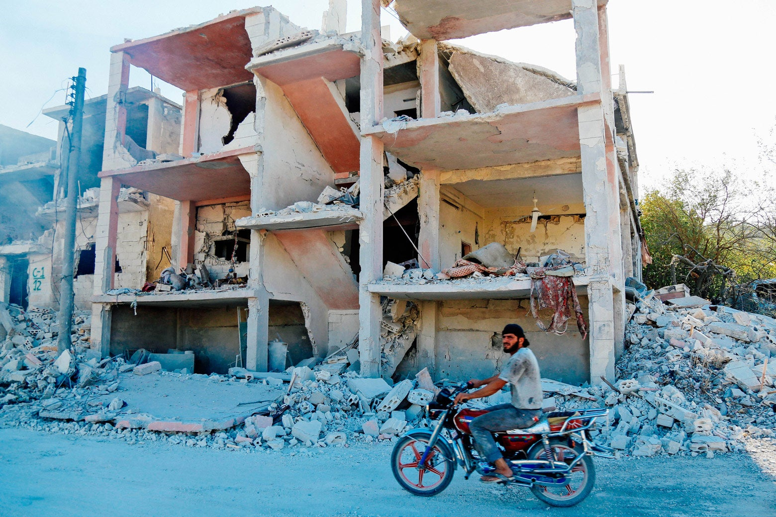A Syrian man rides a motorcycle past a destroyed building.