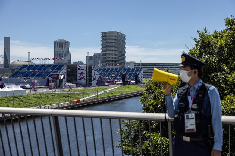 A police officer shouts into a megaphone to tell people not to gather near Ariake Urban Sports Park during the Men's Park final skateboarding competition on day 13 of the Tokyo Olympics on August 5, 2021 in Tokyo, Japan.