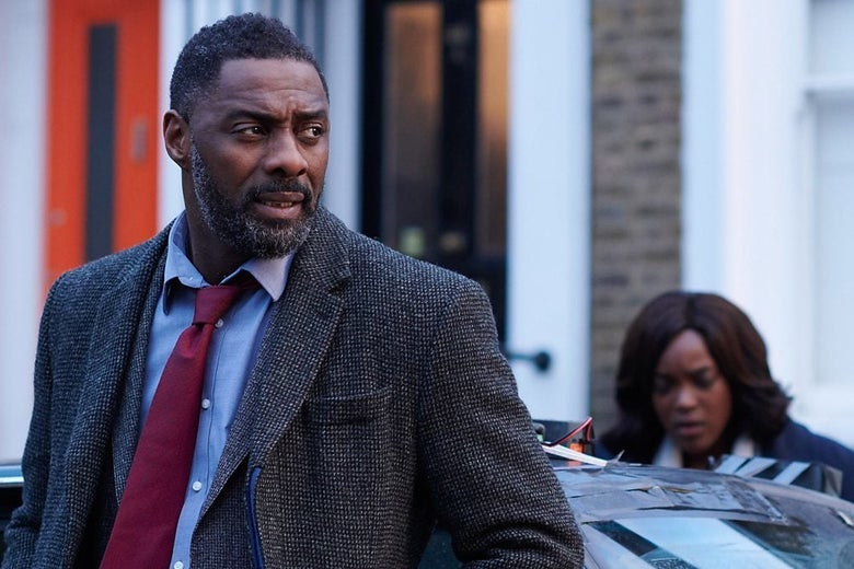 Idris Elba stands in front of a car. Wunmi Mosaku, blurry, in the background.