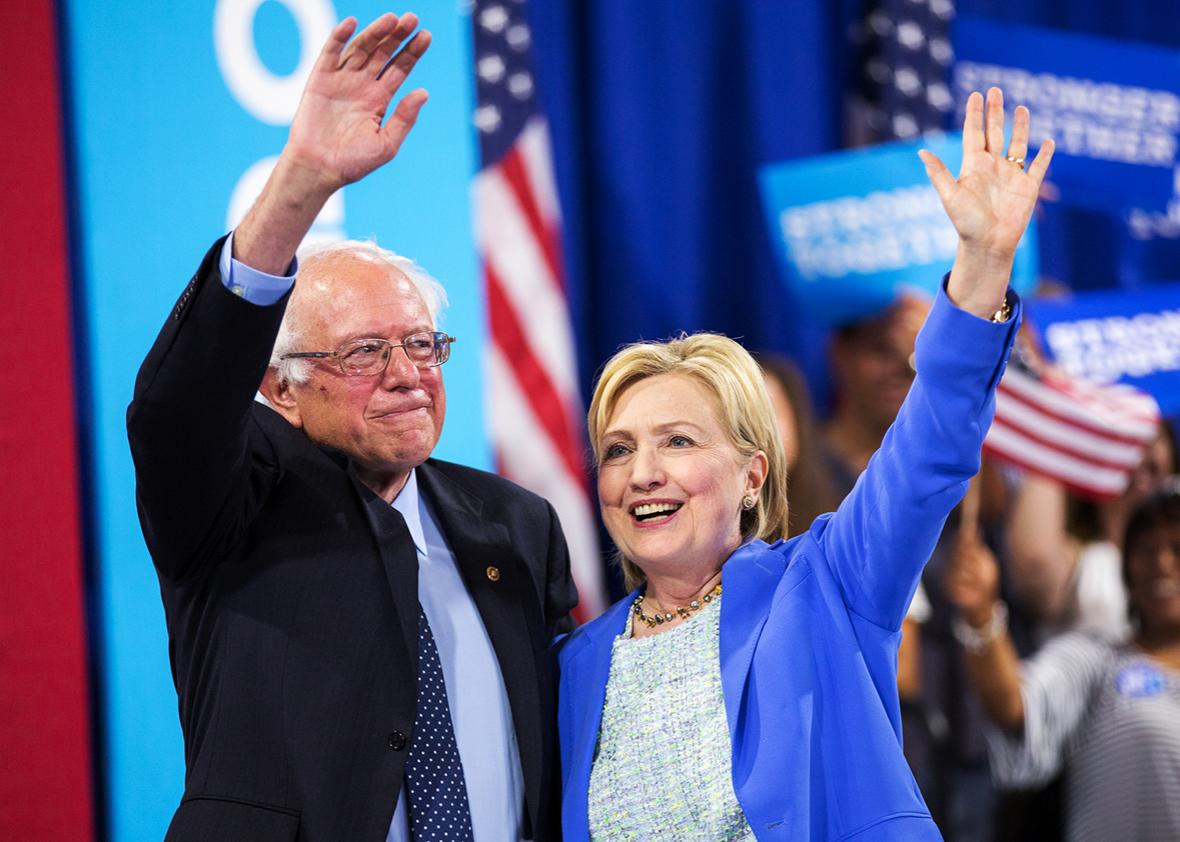Presumptive Democratic presidential candidate Hillary Clinton and Bernie Sanders waves after speaking at a rally in Portsmouth, New Hampshire on July 12, 2016 where she received Sanders' endorsement.