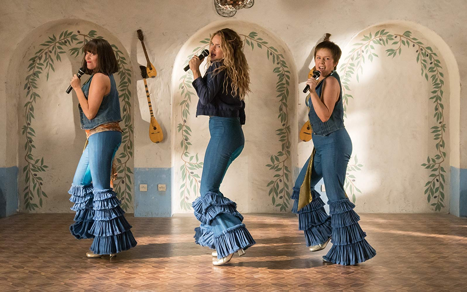 Three women in flared, ruffled denim jeans hold microphones.
