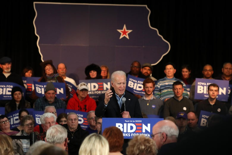 "Biden speaks surrounded by ""Biden Works for Iowa"" signs. Behind him is an outline of the U.S., with a star over Iowa."