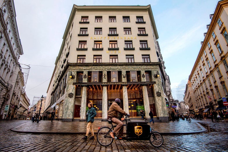 A UPS biker rides their bike in the street in front of the Looshaus.