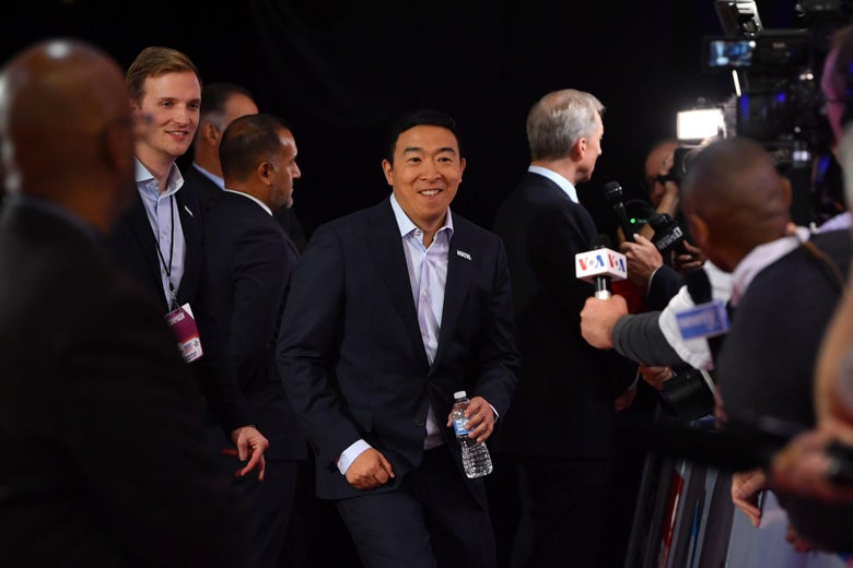 Andrew Yang enters a room full of reporters.