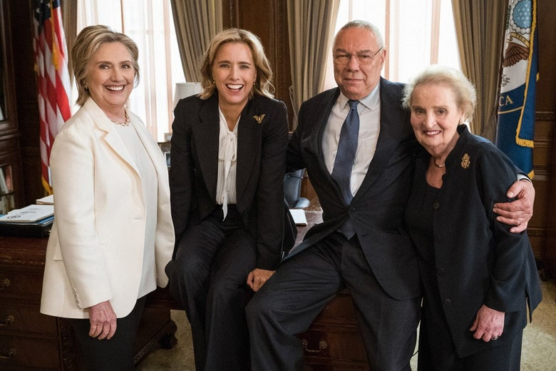 Hillary Clinton, Téa Leoni, Colin Powell, Madeleine Albright smile on a set resembling the Oval Office.