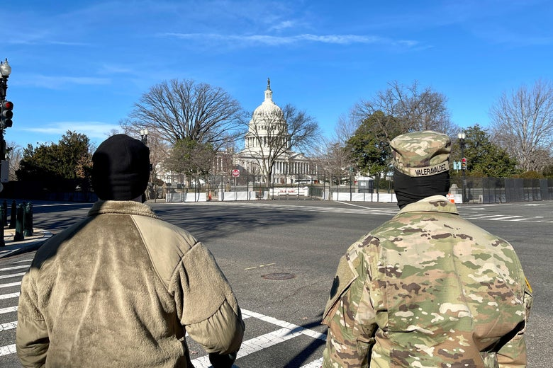 Two National Guard members seen from the back, standing in an intersection, as they look toward the Capitol dome and grounds, which are surrounded by a new security fence