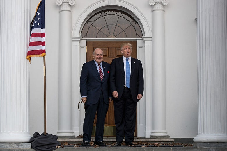 Rudy Giuliani and Donald Trump stand outside the door of a fancy-seeming white building.