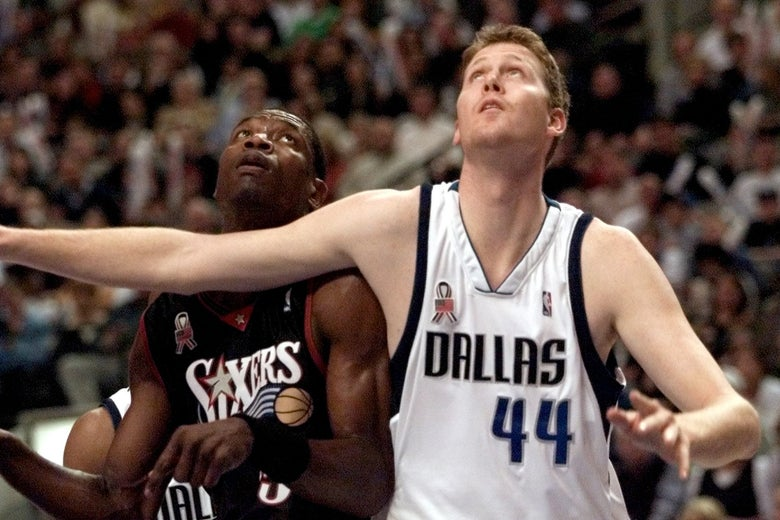 Philadelphia 76ers center Dikembe Mutombo and Dallas Mavericks center Shawn Bradley battle for position under the basket during a 2001 NBA game