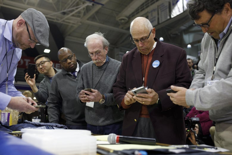 Men, standing in a row, look at their smartphones.