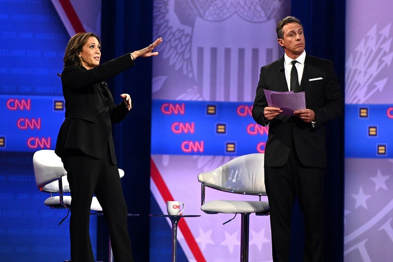 Kamala Harris points out toward the audience as Chris Cuomo stands beside her holding documents.