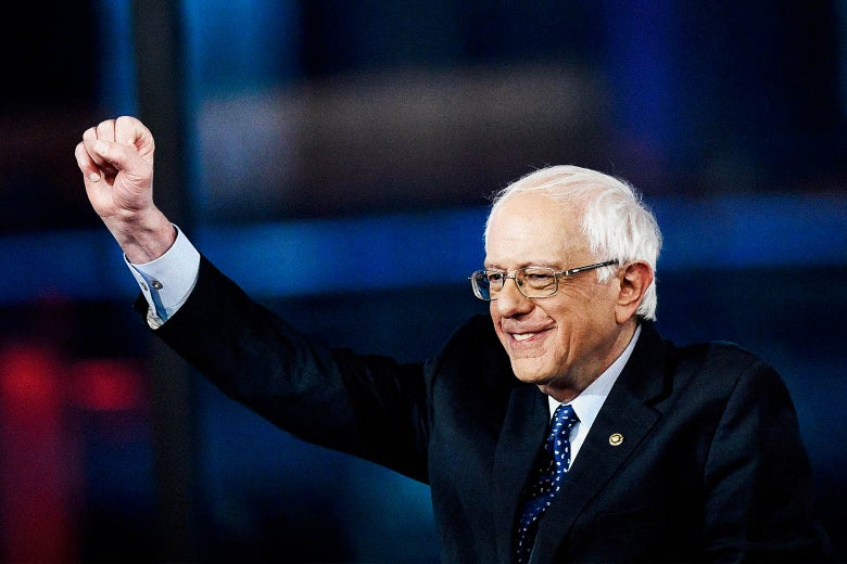 Sanders smiles and raises his fist onstage.