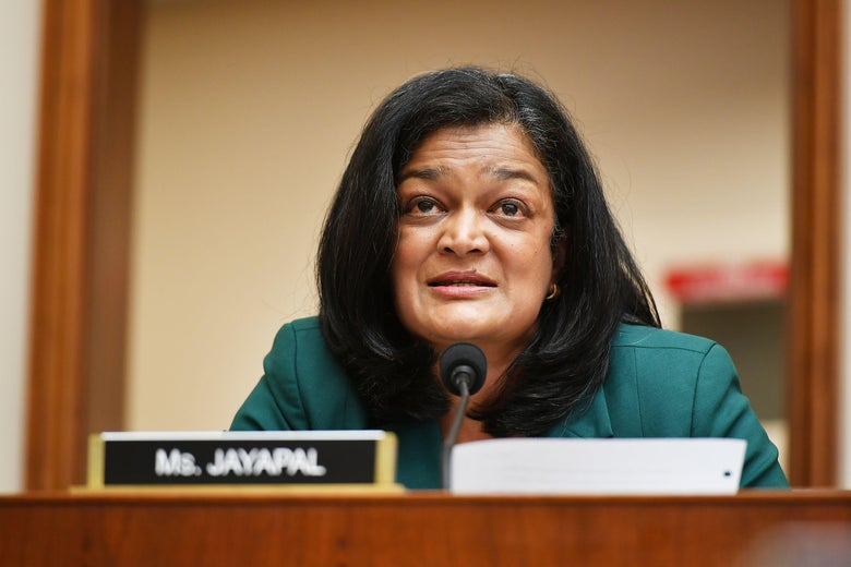 "Pramila Jayapal speaks into a microphone. In front of her is a sign that says ""Ms. Jayapal."""