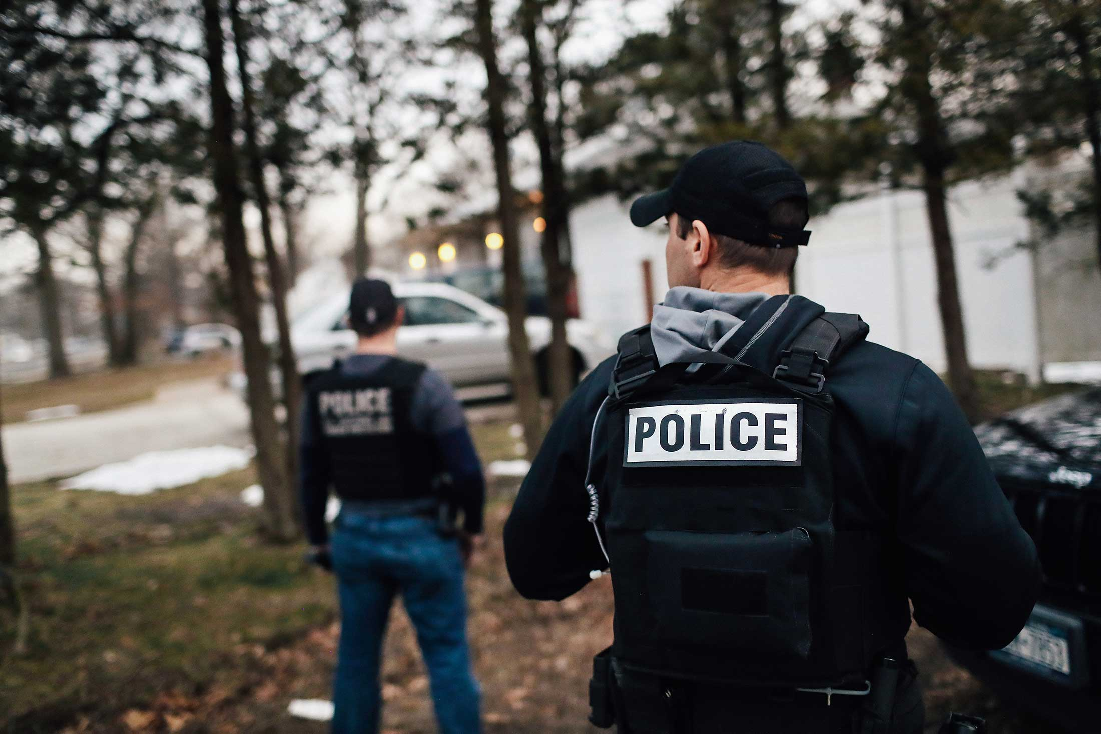"Unidentified men wearing ""POLICE"" vests stand outside a house."