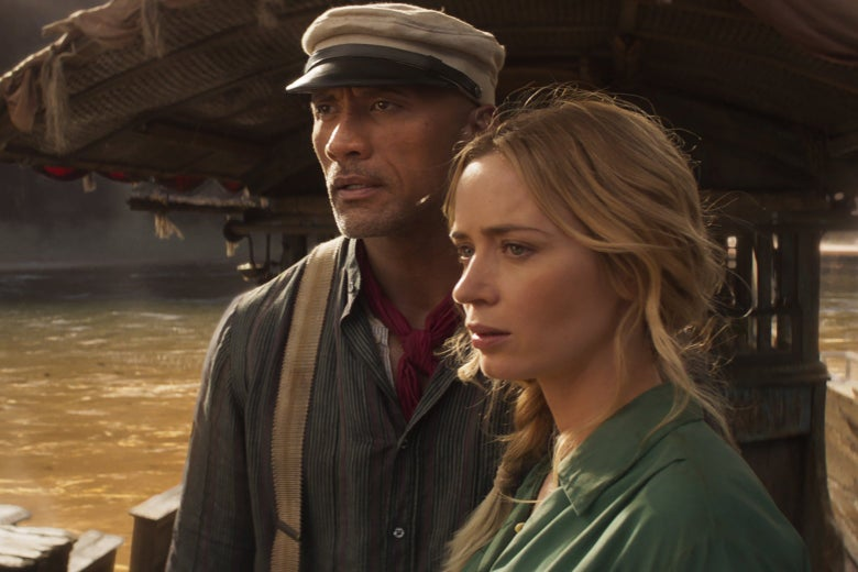 Dwayne The Rock Johnson and Emily Blunt stand on a boat in a still from Jungle Cruise.