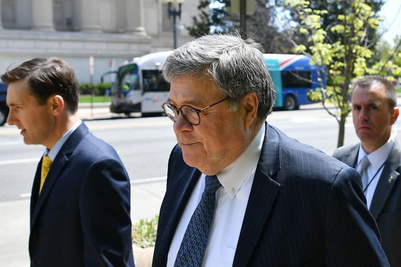 Barr, wearing a suit, walks on a sidewalk with a half-smile on his face.