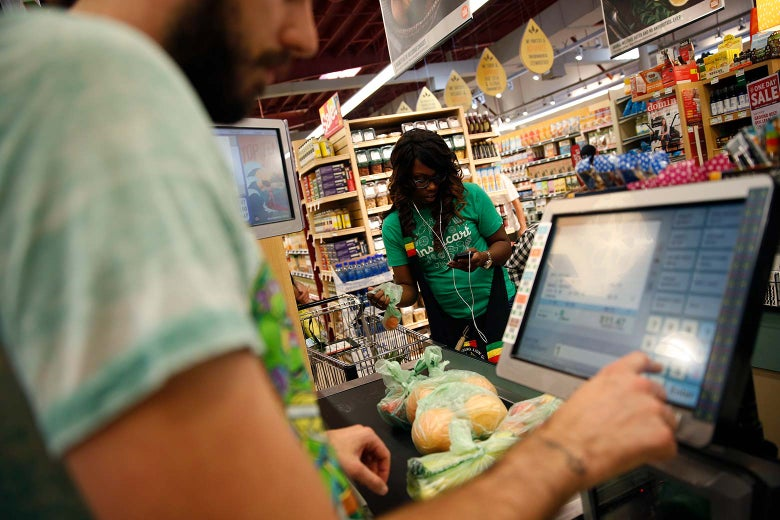 Whole Foods cashier Jason Ellsworth rings up groceries as Instacart shopper Kara Pete double checks her smartphone for items ordered by customer Tricia Carr.