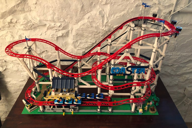 A Lego rollercoaster sitting on a table, complete with moving-looking carts and flags flying high