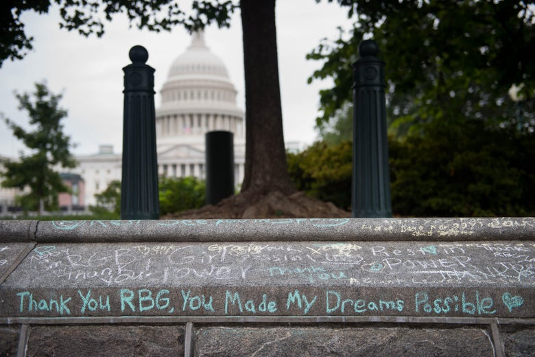 "Chalk inscriptions to RBG, including ""Thank you RBG, you made my dreams possible"" are seen on a wall near the Capitol."