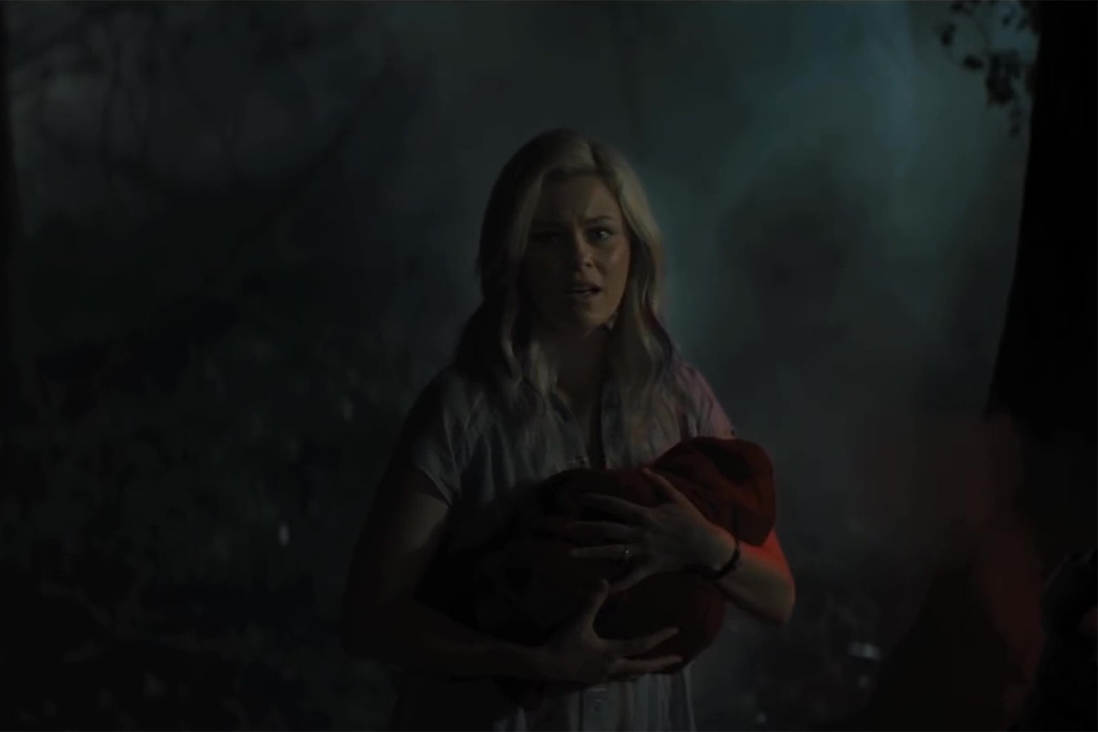 Elizabeth Banks in the middle of the woods, holding a baby wrapped in a red cape.