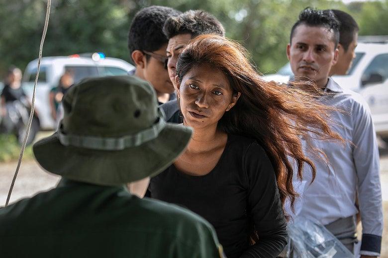 A Border Patrol agent talks to a woman.