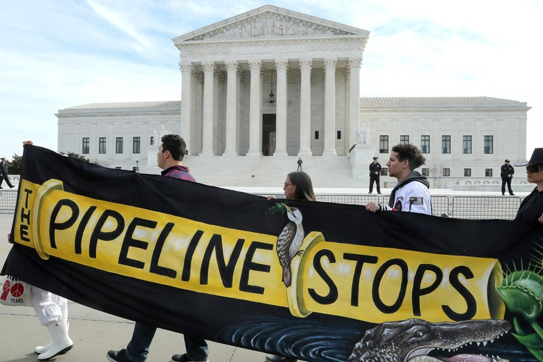 "Protesters walk in front of the Supreme Court holding a banner with a picture of a pipeline on it saying ""The Pipeline Stops."""