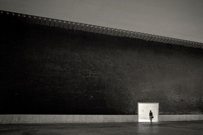 A woman standing alone in a vast, dark, empty hall.
