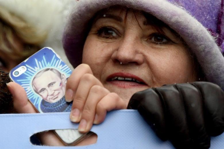 A woman holds a smartphone bearing an image of Russian President Vladimir Putin.
