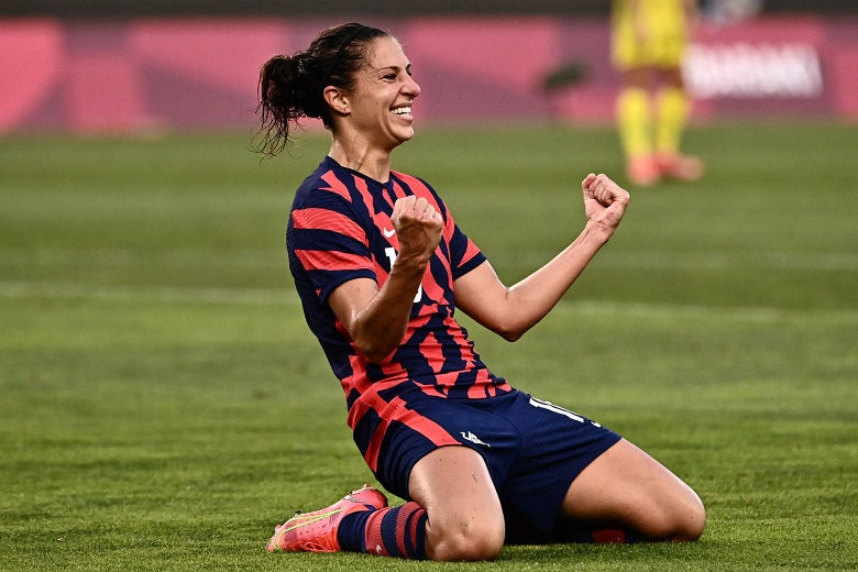 Lloyd grinning and raising her fists as she kneels on the pitch in celebration