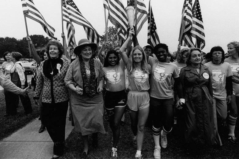 Women hold hands, smile, and carry torches and flags aloft.