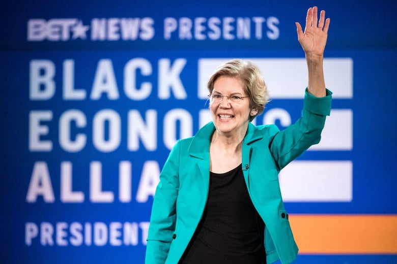 Warren waves to a crowd with her left hand.
