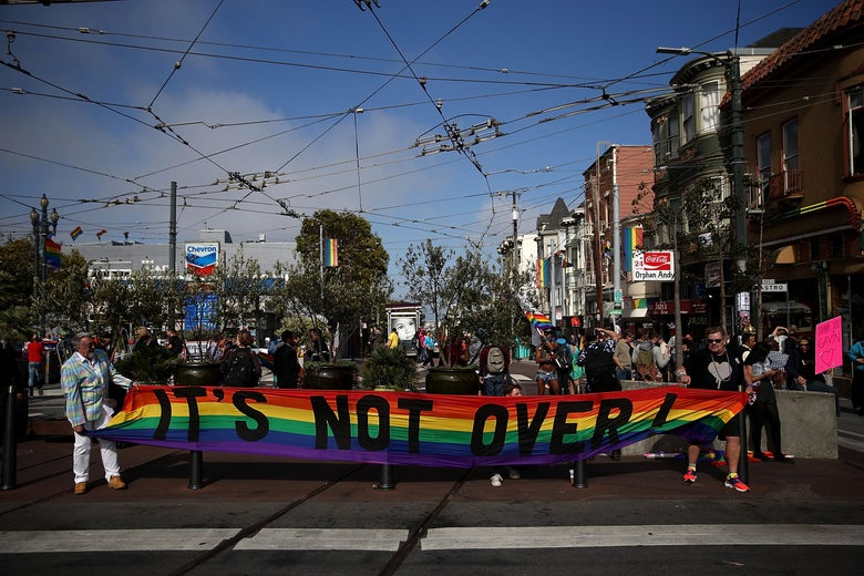 """Same-sex marriage supporters take to the streets in celebration. In the foreground, two people hold a rainbow banner that says """"It's not over!"""""""