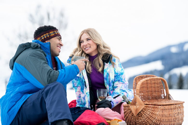A man and a woman on a picnic in the snow.