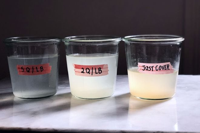 """Three containers of murky pasta water sitting on a marble countertop from most to least transparent: 5q/lb, 2q/lb, """"just cover."""""""
