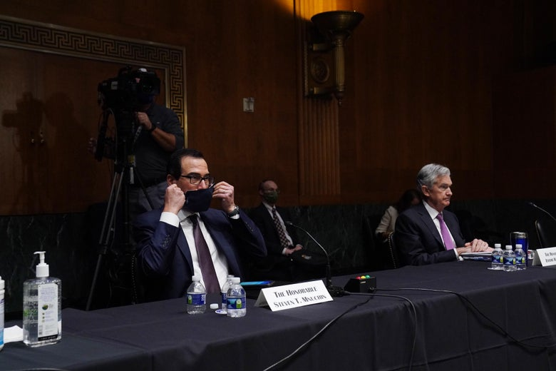 Mnuchin puts on a mask while sitting next to Jerome Powell at a long table in a Senate hearing room