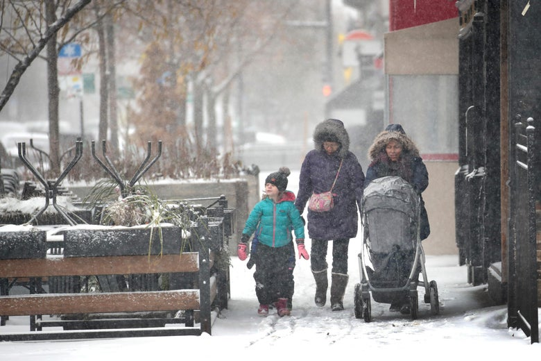People navigate snow-covered sidewalks in Chicago.