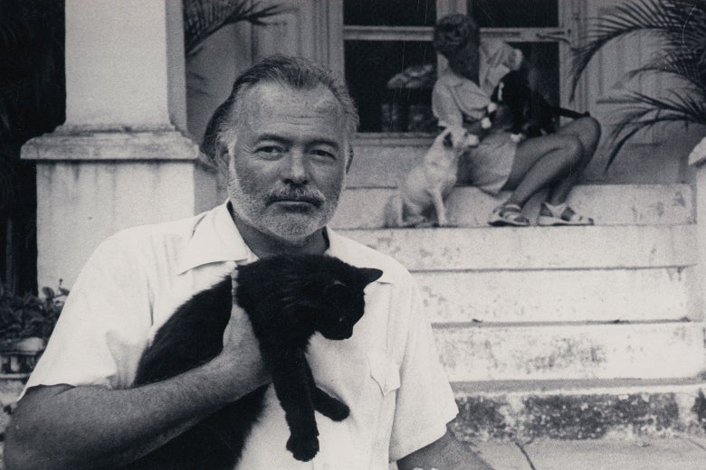 Hemingway holds a cat while standing in front of a porch. A woman and a dog can be seen sitting on the steps behind him.