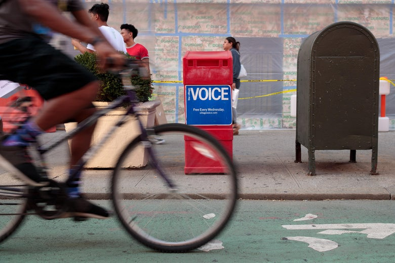 People pass by a Village Voice newspaper stand in the East Village neighborhood in Manhattan, Aug. 22, 2017.