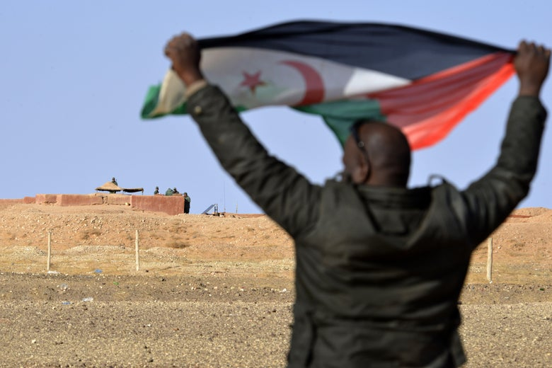 "A Saharawi man holds up a Polisario Front flag in the Al-Mahbes area near Moroccan soldiers guarding the wall separating the Polisario controlled Western Sahara from Morocco on February 3, 2017. - It is the world's oldest functioning security barrier, dubbed a wall of ""shame"" and ""death"" by Western Sahara residents and leaders who want independence from Morocco. (Photo by STRINGER / AFP) / TO GO WITH AFP STORY BY AMAL BELALLOUFI        (Photo credit should read STRINGER/AFP via Getty Images)"