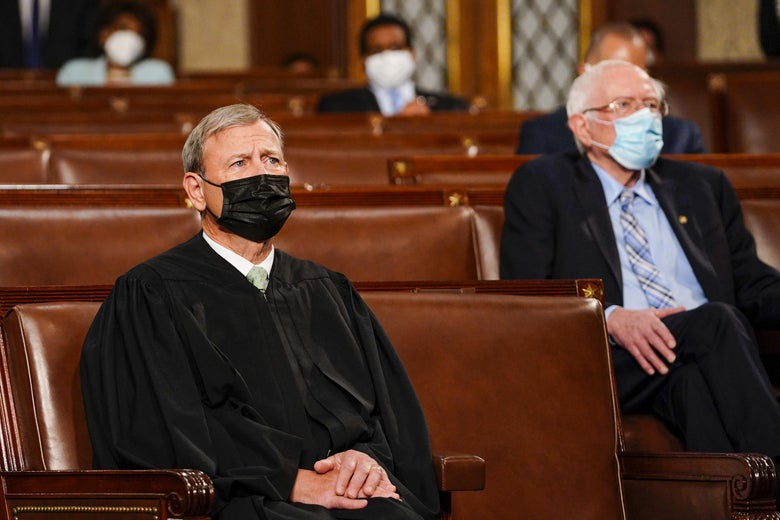 Chief Justice John Roberts and Sen. Bernie Sanders sitting near each other at the State of the Union, wearing masks.