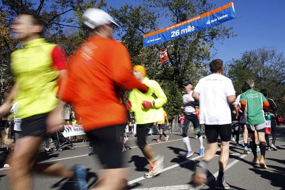 Runners pass the 26 mile marker sign while participating in one of several fun runs in and around Central Park, New York.