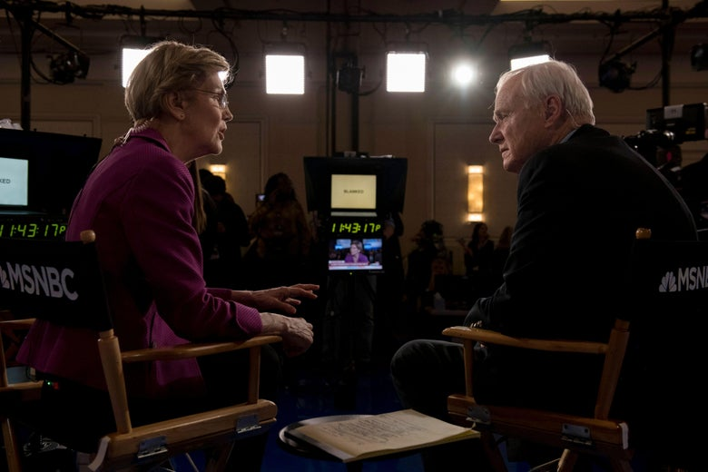 Elizabeth Warren and Chris Matthews speak together in the spin room after the South Carolina debate, sitting in folding chairs, cameras visible.