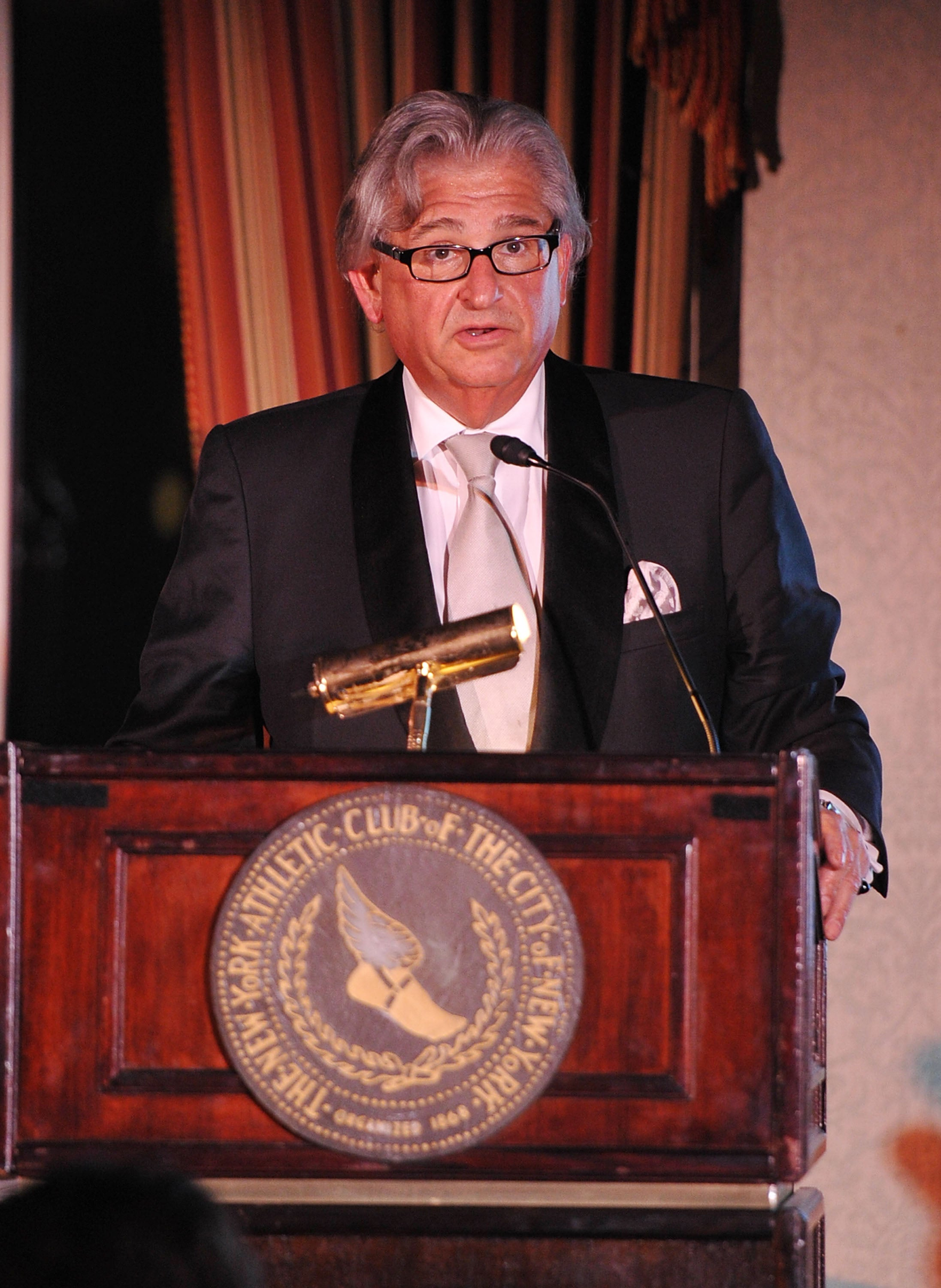 A man with silver hair dressed in a suit speaks at a lectern.
