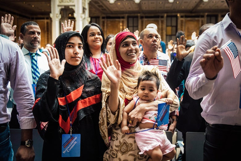 Mosammat Rasheda Akter, originally from Bangladesh, holds her 7-month-old daughter, Fahmida, as she recites the oath of allegiance during a naturalization ceremony.