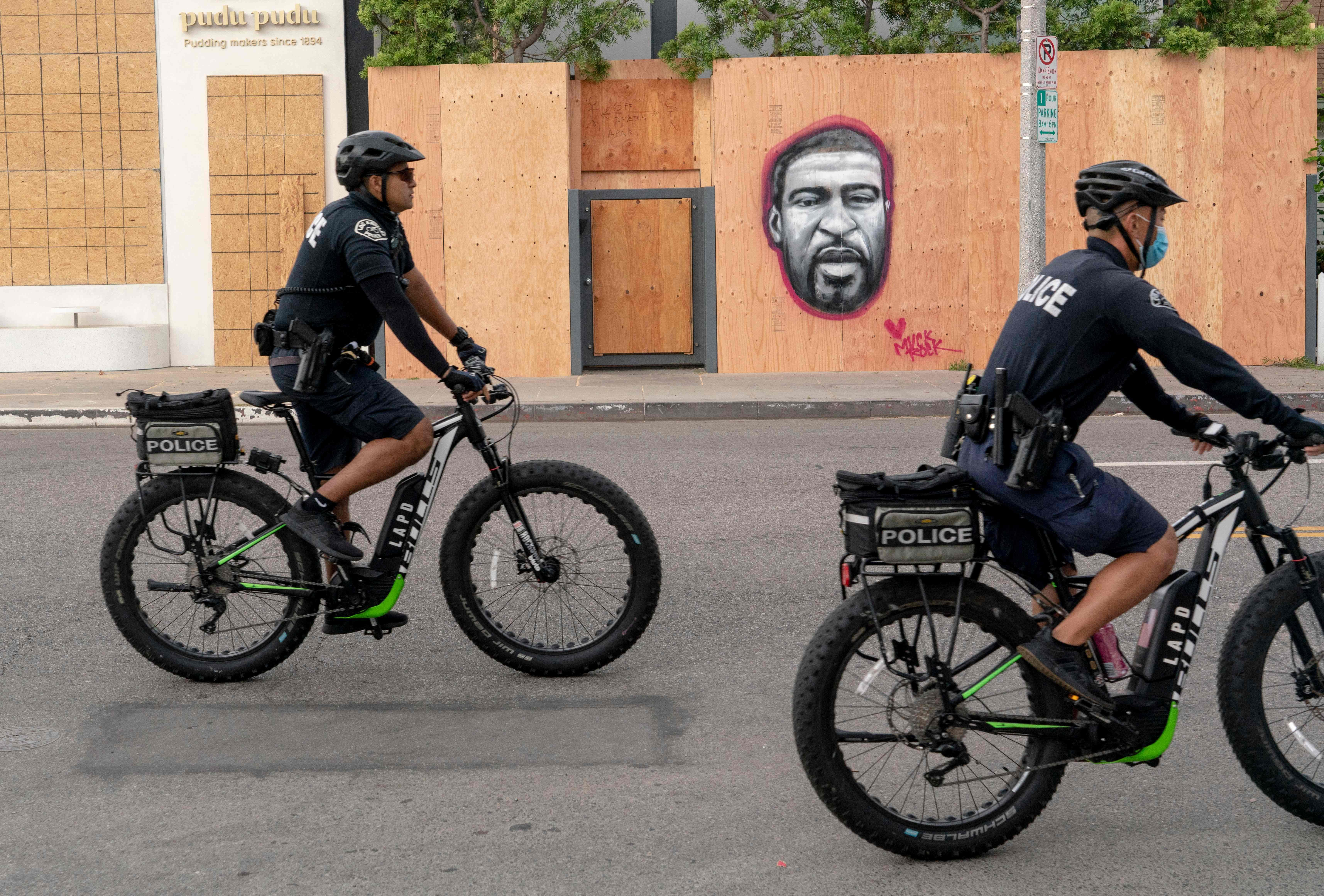 Police officers ride bicycles past a mural of George Floyd in the Venice area of Los Angeles on June 2, 2020.