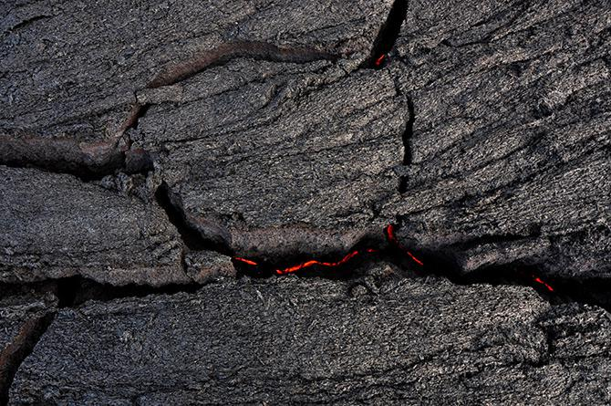 The lava flow is driven by a continual supply of molten rock just beneath the black crust, which rises and cracks as it is driven upward from below.
