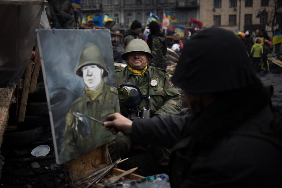 An artist paints the portrait of a protester wearing a full military outfit on a barricade in Kiev on Feb. 16, 2014.