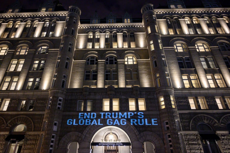 END TRUMP'S GLOBAL GAG RULE is projected in blue light on the front of dramatic-looking hotel at night.