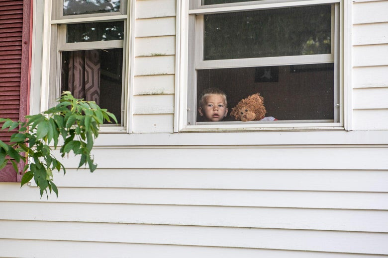 A boy with a stuffed animal beside him looks out a window