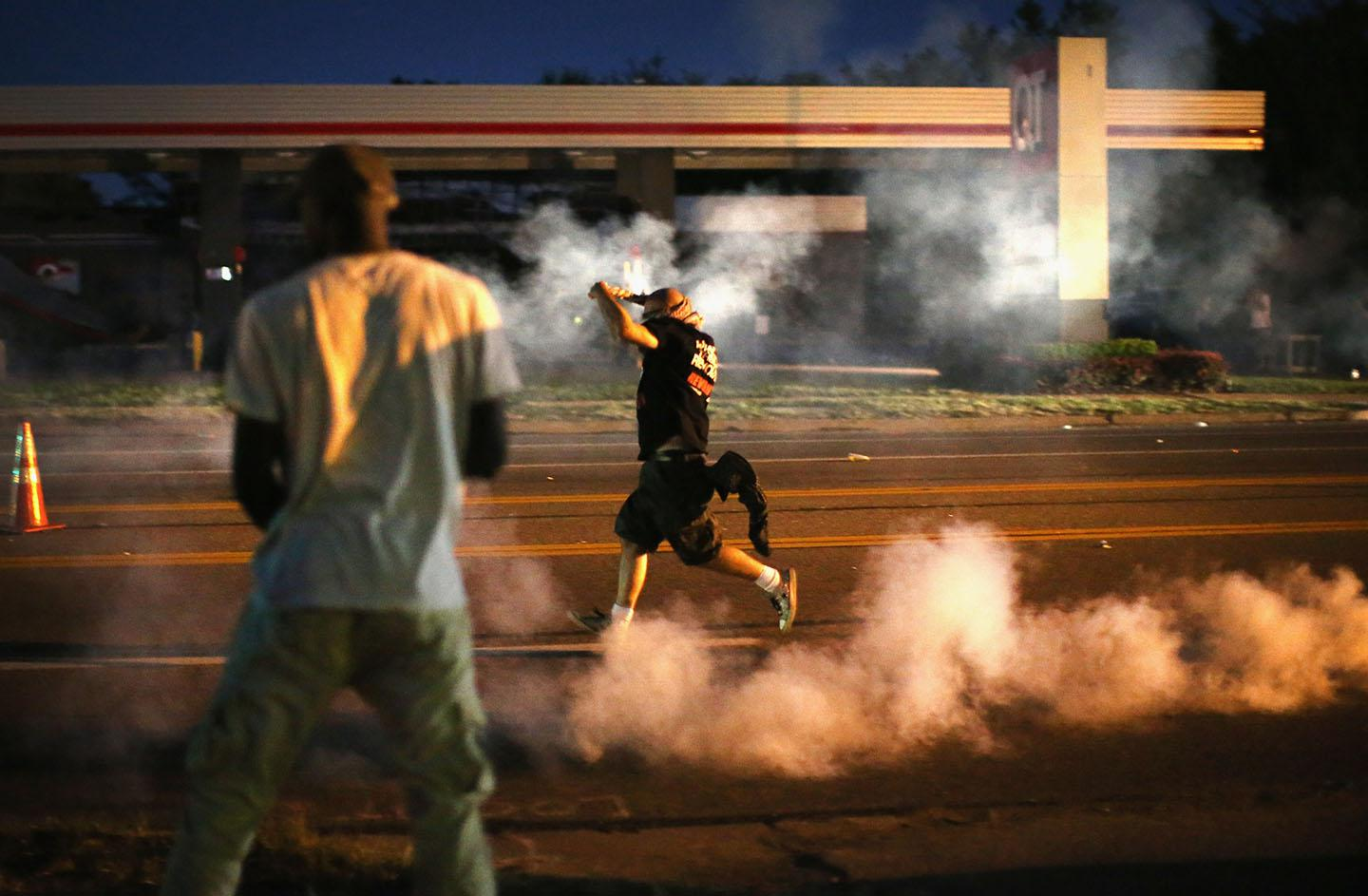 Demonstrators, protesting the shooting death of teenager Michael Brown, scramble for cover as police fire tear gas on August 13, 2014 in Ferguson, Missouri.