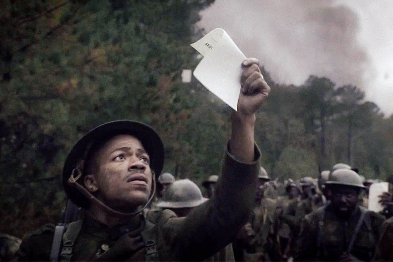 Steven G. Norfleet, dressed in a World War I uniform, catches a propaganda flyer in the air as he marches in a still from Watchmen.